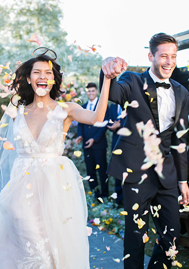 Bride and groom happily exit the ceremony with petals sprinkled in the air.