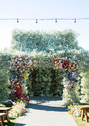 Finished archway of baby's breath and colorful roses.