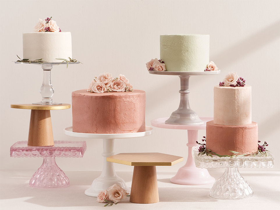 A variety of cakes in different sizes, colors and on different cake stands.