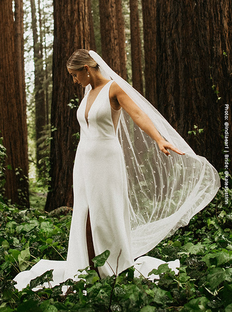 Bride holds out her long veil as she stands in a green forest of plants in the modern Holloway Gown.