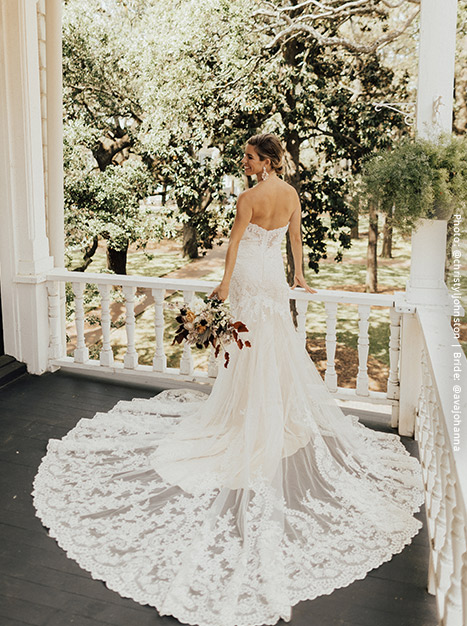 Bride stands on a white-painted porch with a bouquet in hand, showing off the dramatic train on the Leigh Gown.