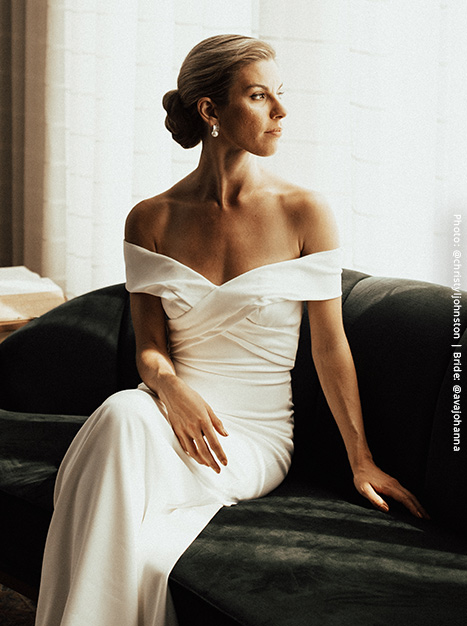 Bride sits on a velvet sofa displaying the off-the-shoulder neckline on the Blake Gown.