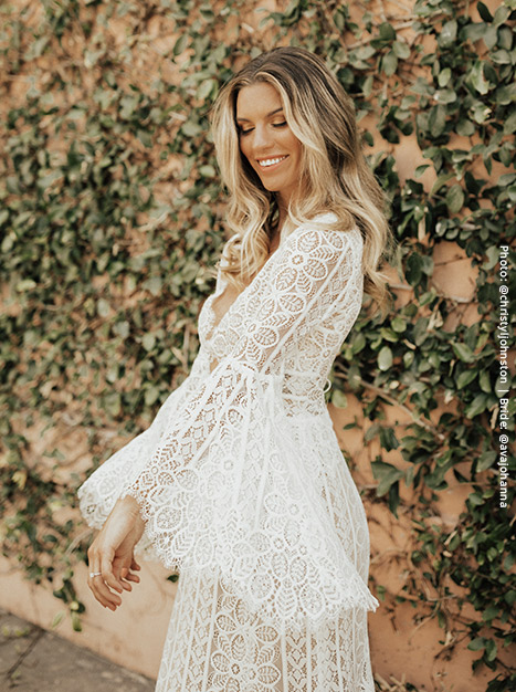 Bride twirls in the lacey Adelaide Gown showing off the flowy bell sleeves.