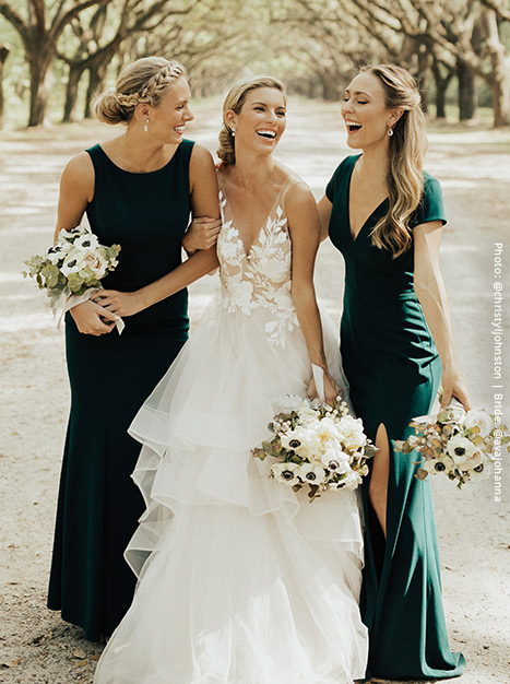 Bride and two bridesmaids dressed in emerald green laugh as they link arms and hold their bouquets of flowers.