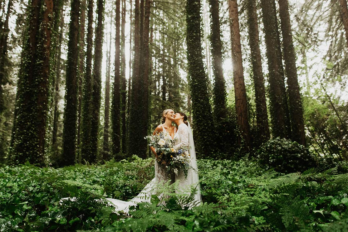 Brides embrace each other as they stand in the middle of the California redwood forest.