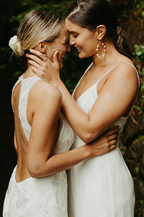 Brides stand close with each other gazing into each other's eyes.