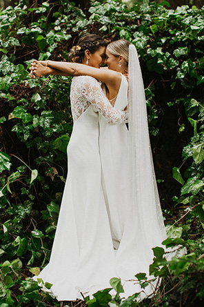 Two brides hug closely in the midst of greenery.