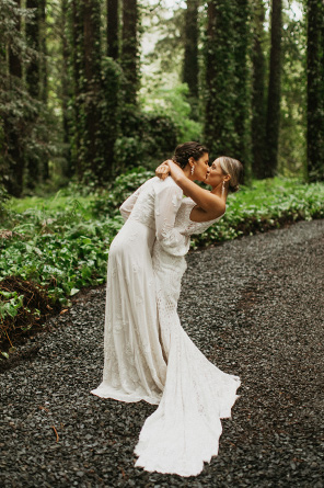 Two Brides kiss on a pathway in the redwood forest.