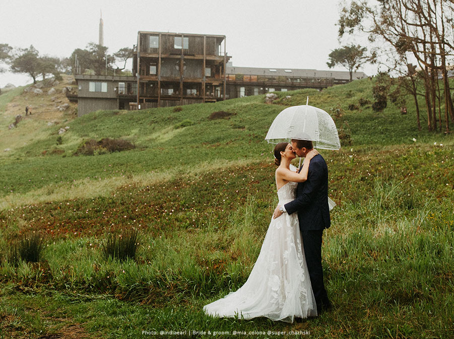 Bride and groom kiss in a rainy open field under a clear umbrella.