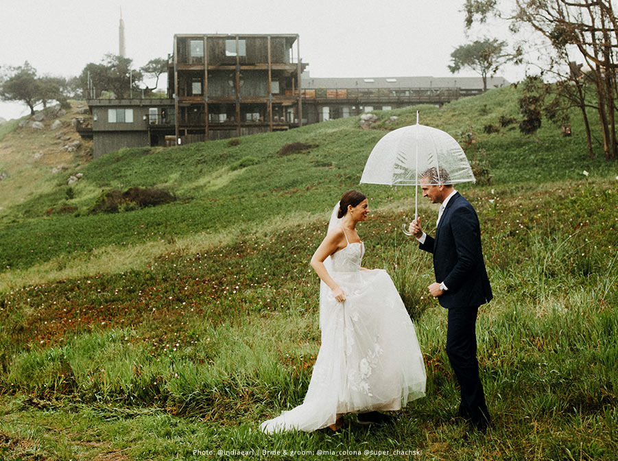 Bride runs to be under the umbrella with her groom.