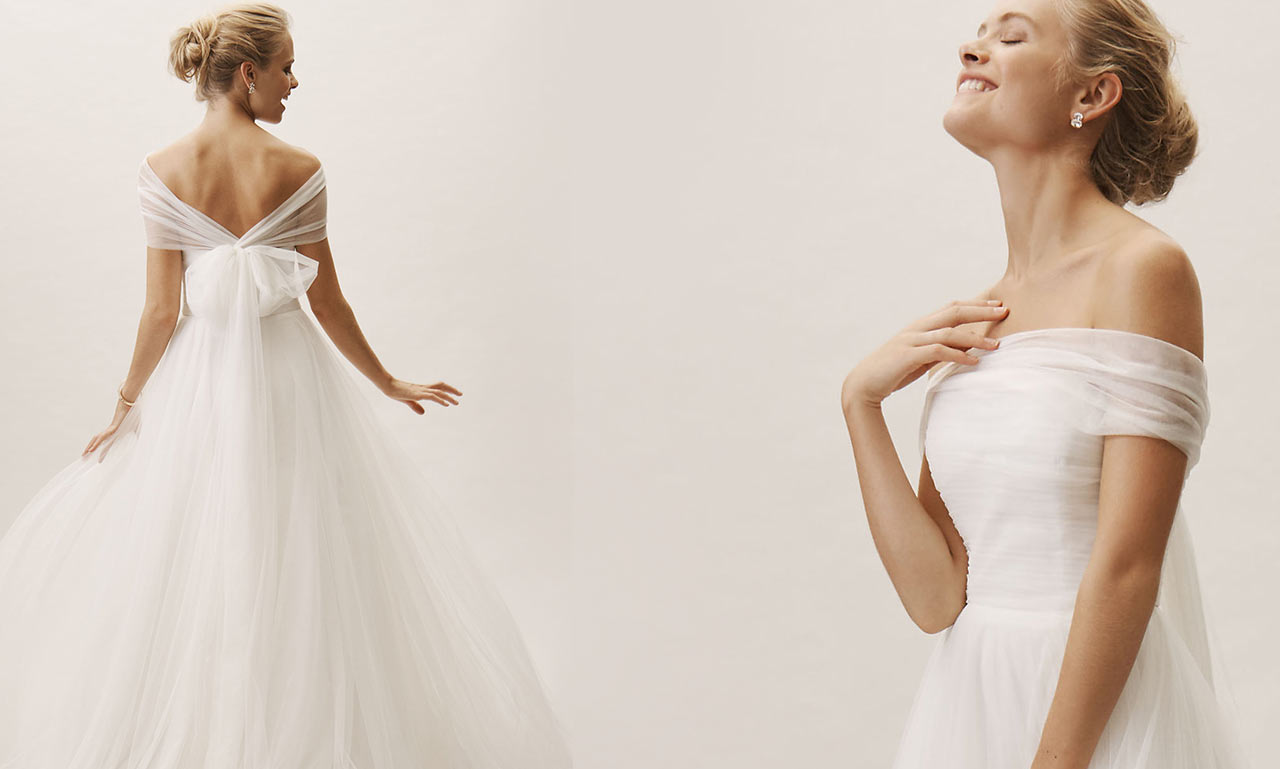 Blonde bride poses with two different angles in the Jillian gown, which fashions tulle in a flowy and off-the-shoulder style.