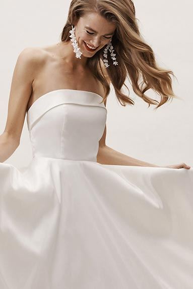 Brunette model shows off strapless modern wedding gown.