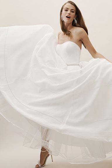 Brunette bride swishes the skirt of the Bellevue strapless bridal gown.