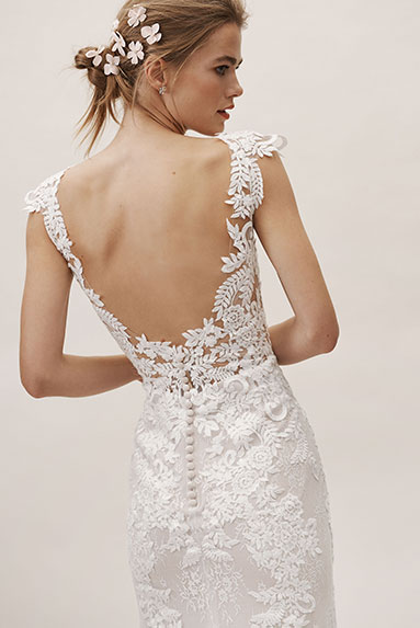 Bride poses to show off the floral lace back of the Milano gown.