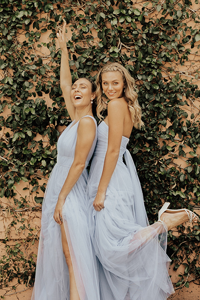 a35457fd604 Two bridesmaids pose in front of an ivy wall in long