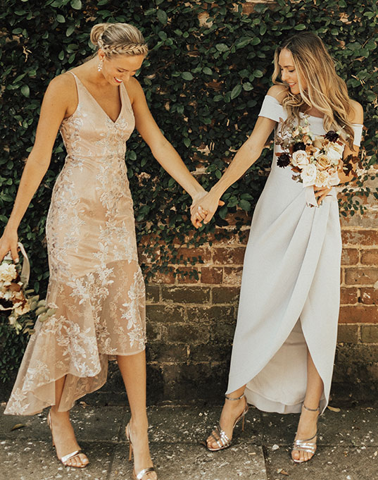 Bride holds the hand of a wedding guest wearing a peach colored midi formal dress.
