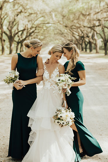 Two bridesmaids surround the bride in their long green bridesmaid dresses.