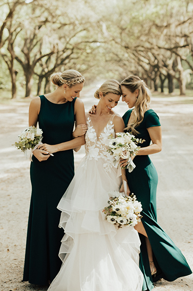 0e179df582f6f Two bridesmaids surround the bride in their long green bridesmaid dresses.