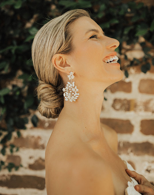 Bride laughs as she shows off her bridal floral earrings.