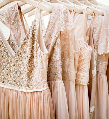 A variety of blush bridesmaid dresses line a rack.