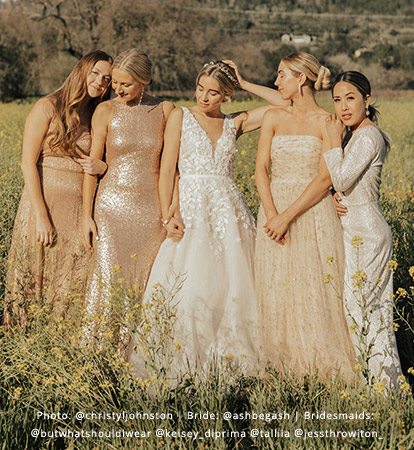 Bridesmaids and Bride link arms while standing in a sunny, golden wildflower field.