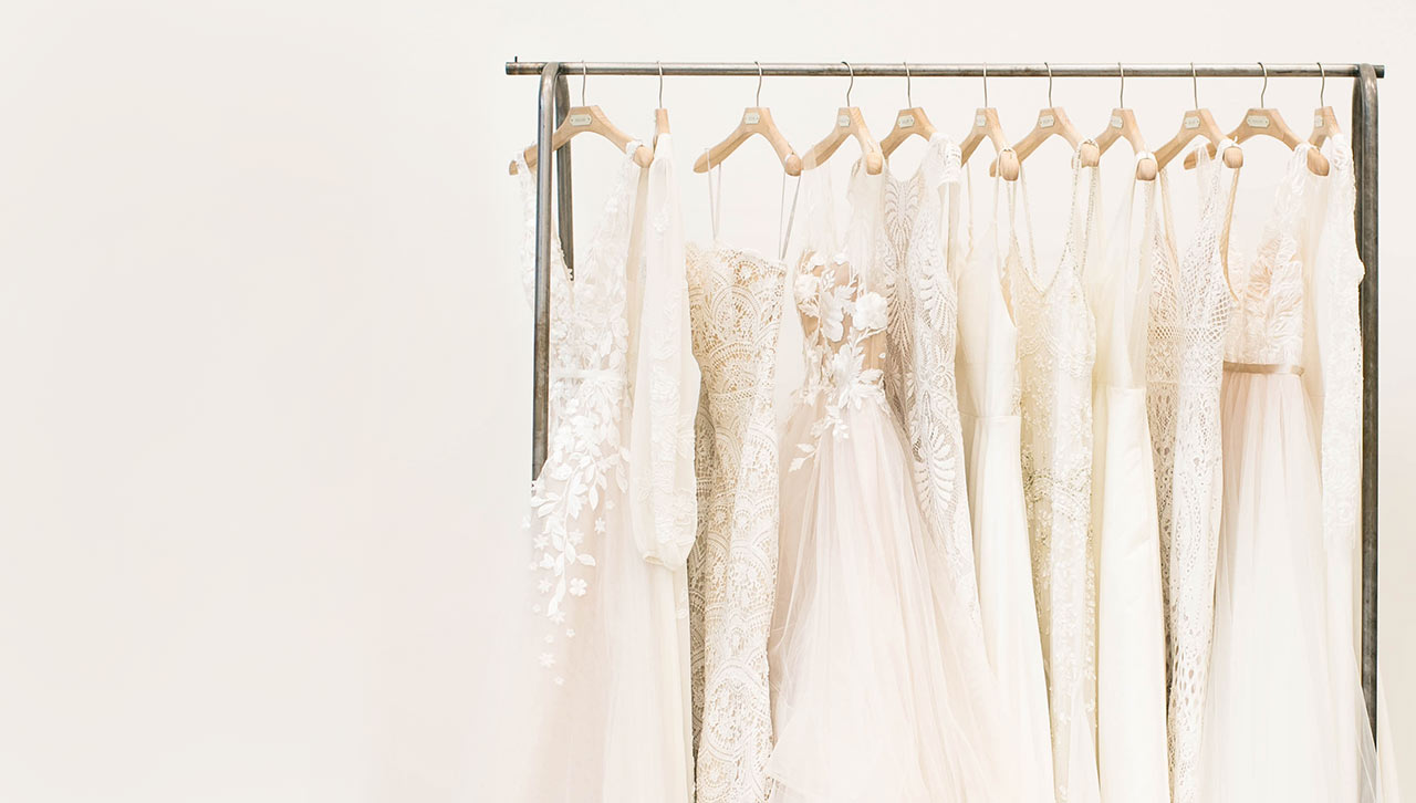 118e0f4975 Shop All Wedding Gowns · A rack of gowns displays a diverse array of styles  to choose from at a BHLDN