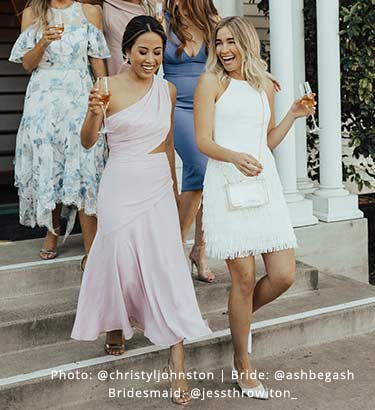Bride, in a littel white dress, and wedding guest, in a pink one-shoulder dress, descent the stairs with champagne in hand.