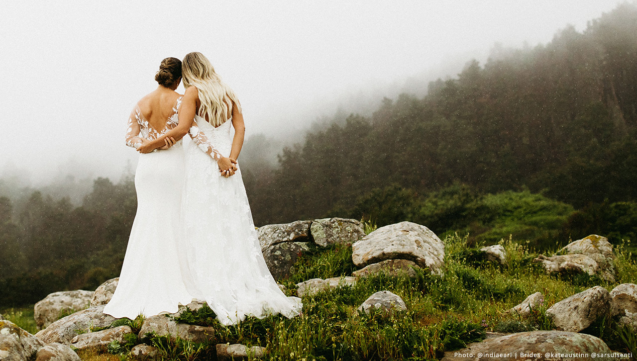 Same sex couple embraces while looking out into a misty forest.