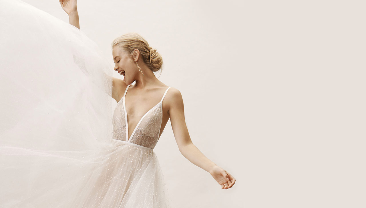 Bride excitedly swishes her tulle gown while smiling.